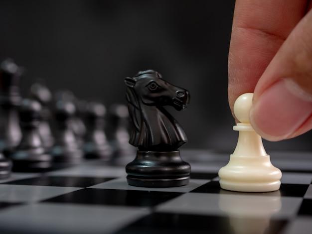 Mão segurando o peão branco movendo-se jogando o jogo de tabuleiro de xadrez