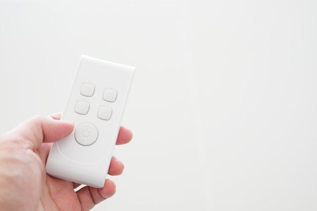 Mão segurando o pequeno controle remoto eletrônico branco.
