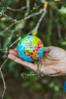 Mão segurando o pequeno globo na natureza
