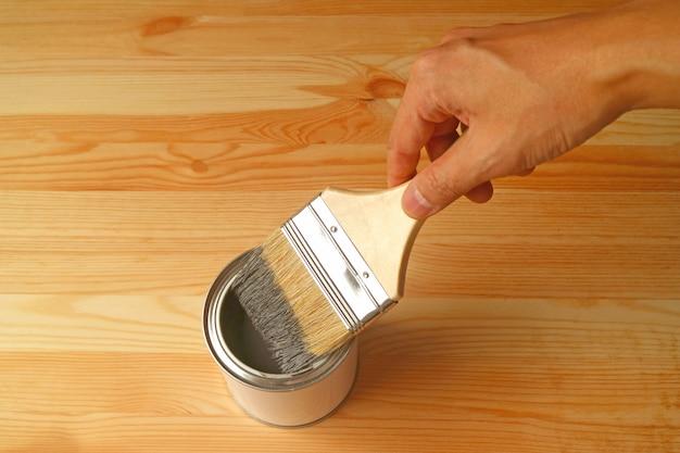 Mão segurando o pincel com tinta na prancha de madeira