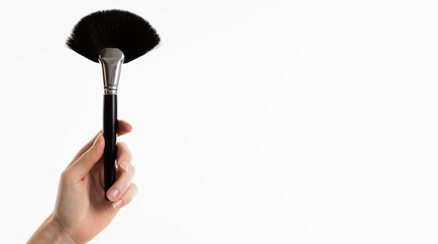 Mão segurando o pincel de maquiagem com espaço de cópia