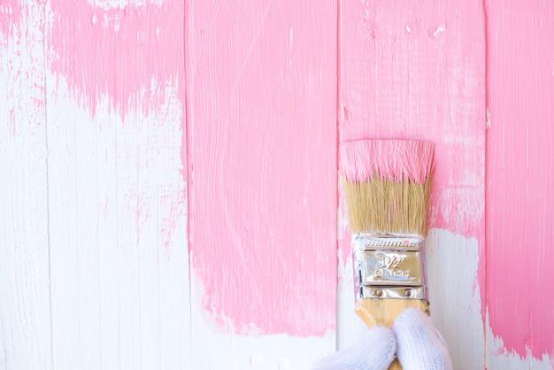 Mão segurando o pincel de pintura cor-de-rosa em uma mesa de madeira branca