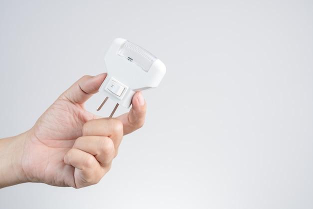 Mão segurando o plugue de luz led de parede e tomada elétrica