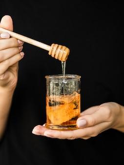 Mão segurando o pote de mel delicioso