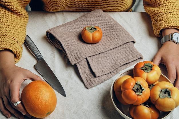 Mão segurando o prato com caquis laranja frescos