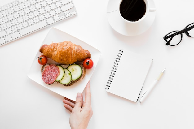 Mão segurando o prato com croissant e sanduíche perto de notebook