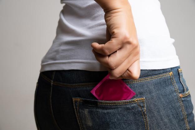 Mão segurando o preservativo no jeans azul, foco seletivo, conceito de sexo seguro