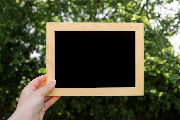 Mão segurando o quadro-negro. lousa vazia, em branco, com espaço de cópia. negócios, educação, aprendendo o conceito.