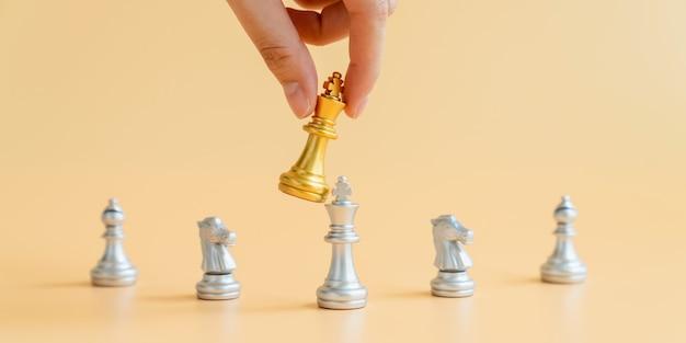Mão segurando o rei do xadrez de ouro sobre o rei do xadrez de prata