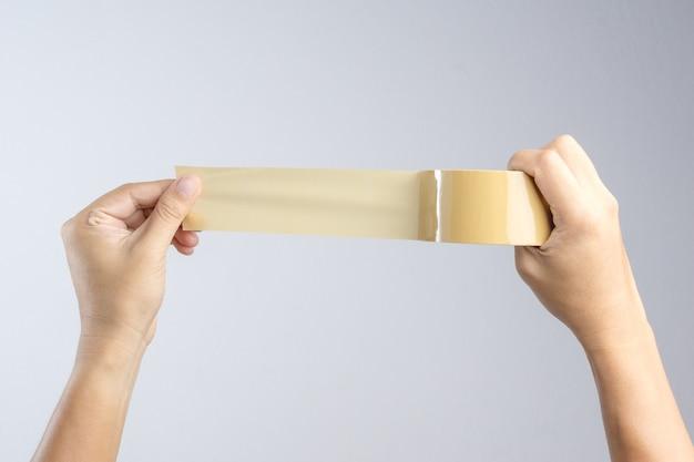 Mão segurando o rolo de fita de embalagem marrom