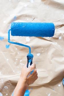 Mão segurando o rolo de pintura sobre papel artesanal com manchas