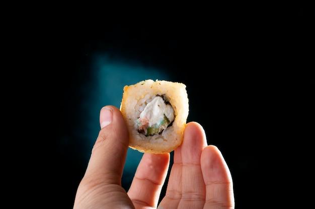 Mão segurando o rolo de sushi, copie o espaço. refeição pronta para comer