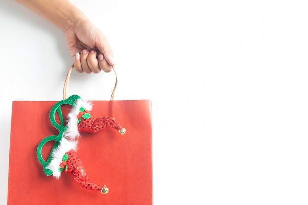 Mão segurando o saco de compras de natal em fundo branco