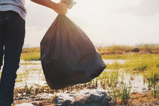 Mão segurando o saco de lixo preto no rio para limpeza com pôr do sol