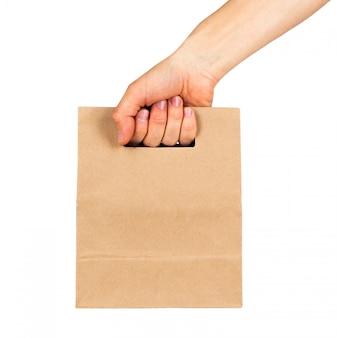 Mão segurando o saco de papel kraft isolado no espaço em branco