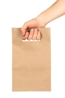 Mão segurando o saco de papel kraft isolado no fundo branco