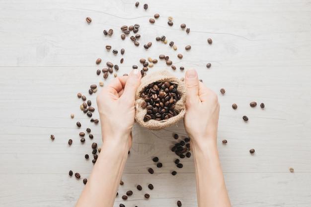 Mão segurando o saco pequeno com grãos de café na mesa de madeira
