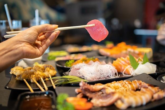 Mão segurando o sashimi de atum usando os pauzinhos