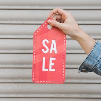 Mão segurando o sinal de venda perto de parede perfilada