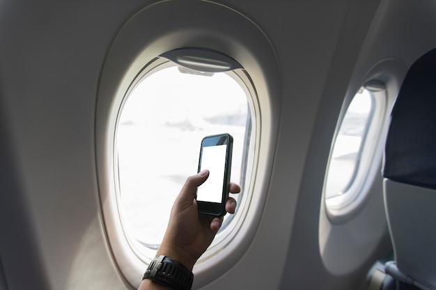 Mão segurando o smartphone a bordo perto do assento da janela