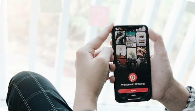 Mão segurando o smartphone com o app pinterest na tela. o pinterest é um quadro de avisos online que permite que as pessoas fixem suas coisas interessantes