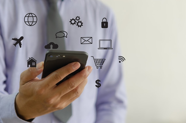 Mão segurando o smartphone com o conceito de ícones. mão usar smartphone compras online conceito de rede de mídia social.