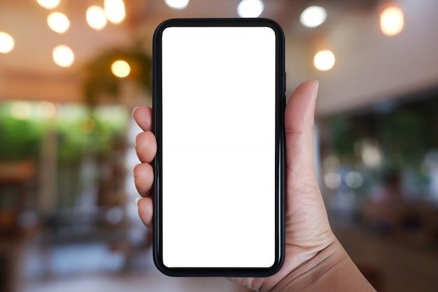 Mão segurando o smartphone com tela em branco para app no interior do café