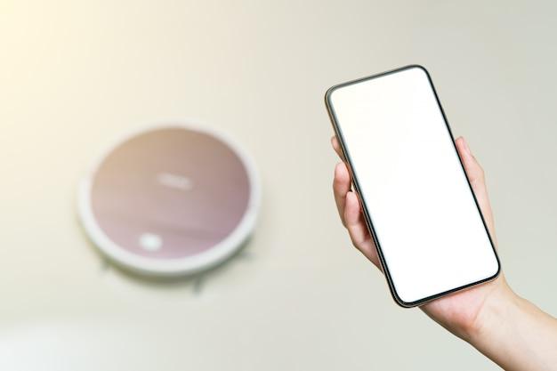 Mão segurando o smartphone com tela em branco para aspirador de pó robótico de controle. conceitos de tecnologia de vida inteligente.