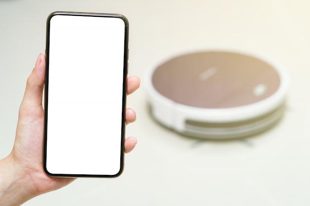 Mão segurando o smartphone com tela em branco para aspirador de pó robótico de controle