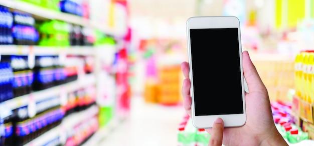 Mão segurando o smartphone com uma tela em branco em um supermercado