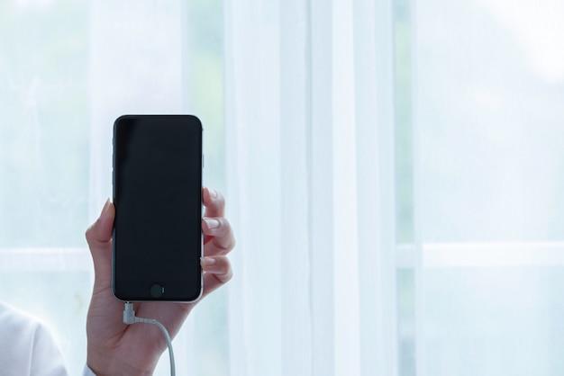 Mão segurando o smartphone conectado com fone de ouvido.