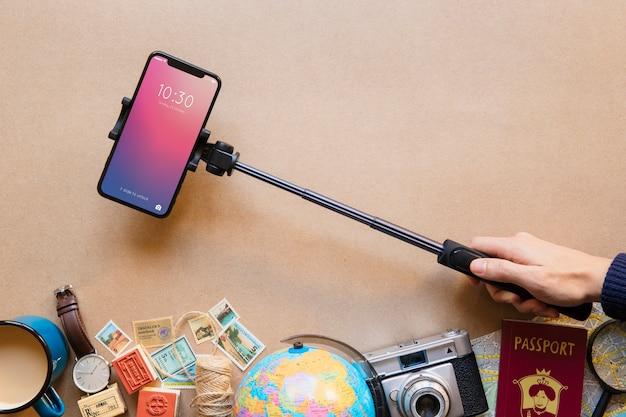 Mão segurando o smartphone de alta tecnologia em monopod Foto gratuita