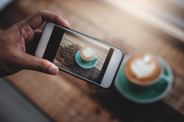 Mão segurando o smartphone e tirando foto de café quente na xícara de café verde na mesa de madeira.
