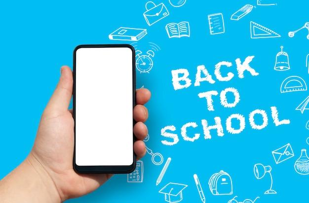 Mão segurando o smartphone em branco de volta ao fundo da escola