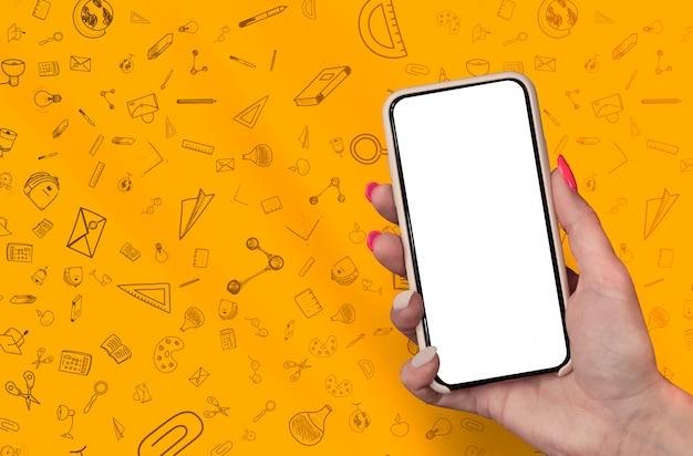 Mão segurando o smartphone em branco na escola de papelaria doodles fundo