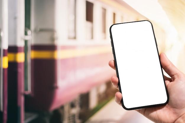 Mão segurando o smartphone na estação de trem