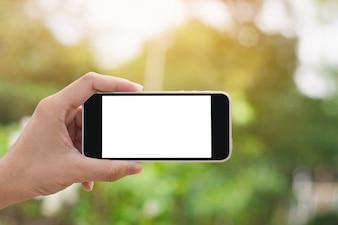 Mão segurando o smartphone no fundo da natureza com espaço de cópia