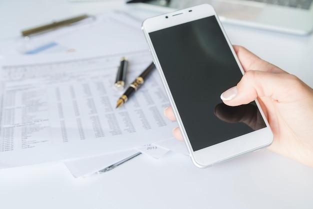 Mão segurando o smartphone no local de trabalho