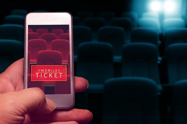 Mão segurando o smartphone para bilhete de cinema reservado. compra de bilhetes online.