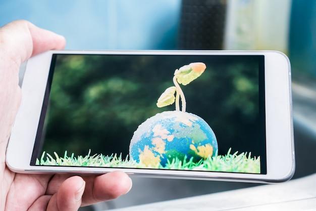 Mão segurando o smartphone para estudar ou pesquisando planta semeadura