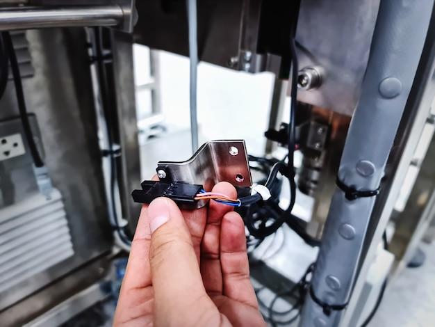 Mão segurando o suporte de aço inoxidável e sensor com fio para máquina automatizada