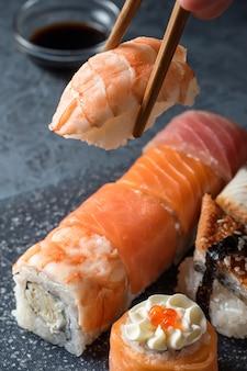 Mão segurando o sushi de pauzinhos com camarão no fundo da mesa cinza