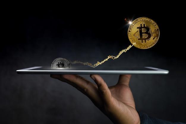 Mão segurando o tablet com bitcoins e gráfico saindo dele em fundo escuro