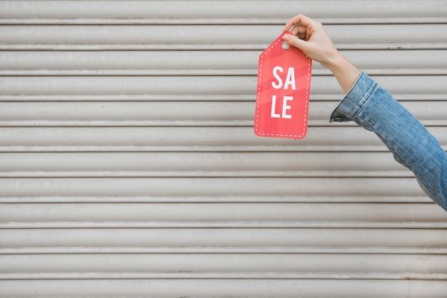 Mão segurando o tablet de venda perto de parede perfilada