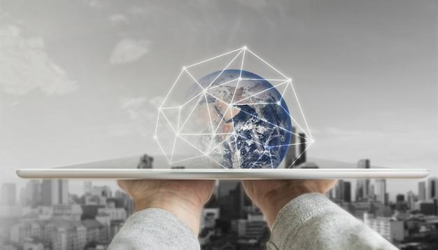 Mão segurando o tablet digital com tecnologia de conexão de rede global e edifícios modernos