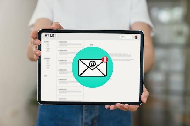 Mão segurando o tablet e mostrar a tela de e-mail no aplicativo móvel no escritório.