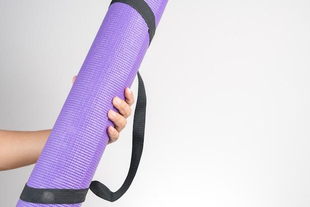 Mão segurando o tapete de yoga, exercício e acessório de fitness