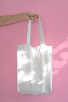 Mão segurando o tecido da lona do saco para modelo em branco de maquete isolado em fundo rosa claro e sombra.