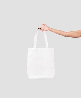 Mão segurando o tecido de lona de saco para modelo em branco de maquete isolado em fundo cinza.