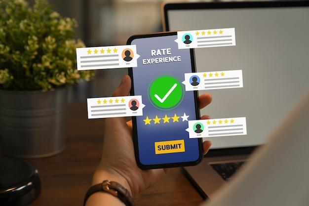 Mão segurando o telefone avalie sua experiência e mostre à tela outros comentários do usuário.